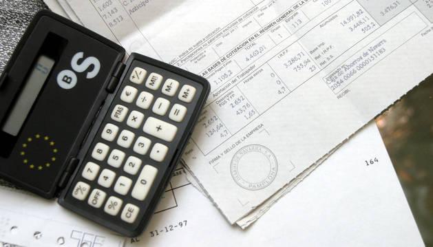 Imagen de una calculadora junto a una nómina.