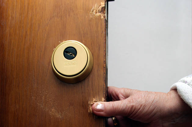 Estado de la puerta de una de las viviendas asaltadas.