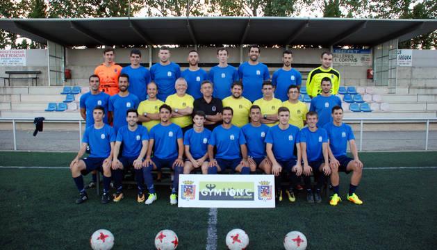 Jugadores, técnicos y presidente del CD Corellano posan juntos sobre el césped artificial del Campo Municipal Ombatillo.