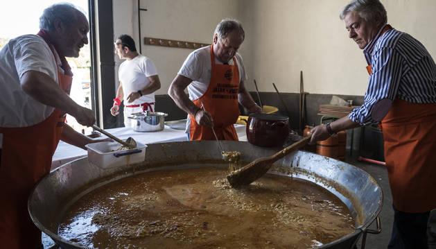 Los cocineros sirven las pochas en perolas que la gente va llevando.