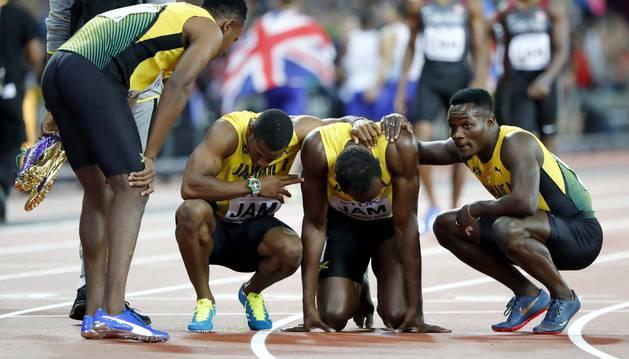 Usain Bolt, arropado por sus compañeros tras sufrir la lesión.