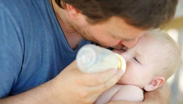Un padre da el biberón a su hijo recién nacido.  Los padres disfrutan de cuatro semanas de permiso de paternidad desde el 1 de enero de 2017.