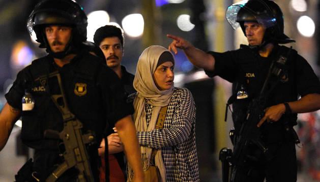 Dos policías acompañan a una pareja musulmana por Las Ramblas tras el atentado.