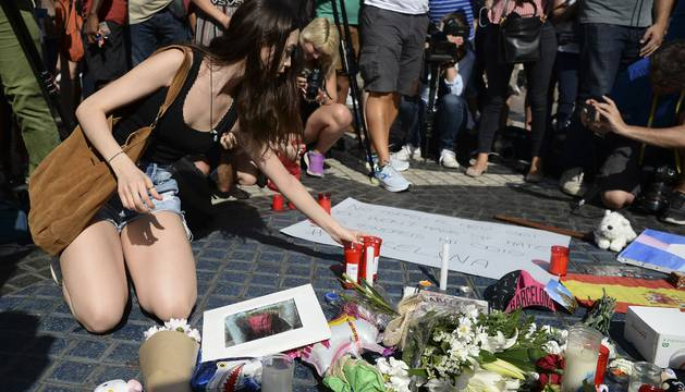 Una mujer deposita una vela en las Ramblas, en homenaje a las víctimas de la matanza de Barcelona del jueves.
