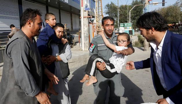 Un policía afgano rescata a un niño herido por la explosión
