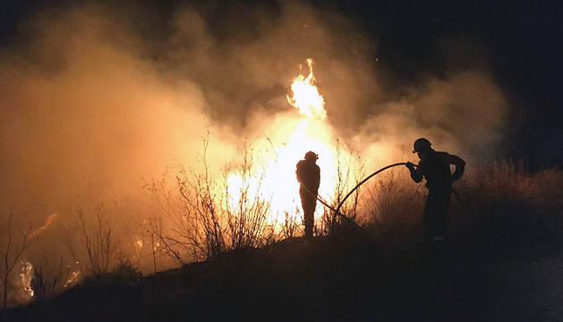 Dos bomberos, durante el fuego registrado en Beire.