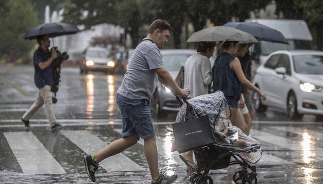 Foto de un hombre corre bajo la lluvia, ayer en Pamplona.