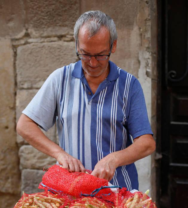 Imagen de un hombre atando los sacos de vainas en Sangüesa durante el día del elogio a la pocha del año pasado.