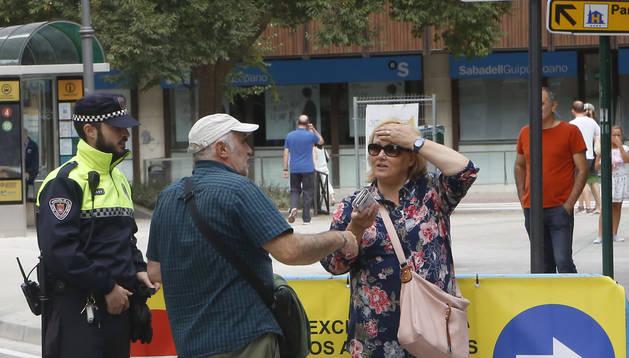 Dos peatones preguntan sobre los cambios de tráfico a un policía municipal a la entrada del paseo Sarasate.