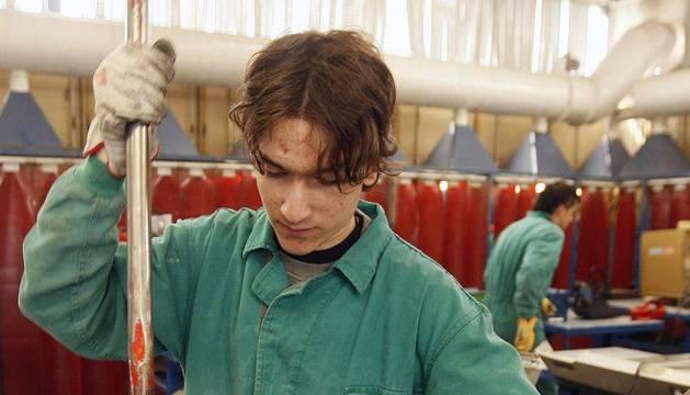 Un joven realiza un trabajo en una fábrica.
