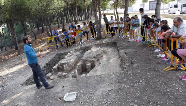 Aitor Alzueta, aficionado a la arqueología y quien descubrió los restos, explica el hallazgo a alumnos del colegio de Ribaforada.