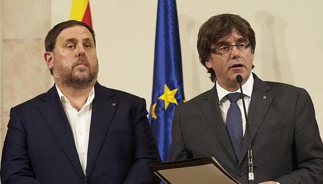 Carles Puigdemont (c), acompañado por el vicepresidente Oriol Junqueras (i) y el conseller de presidencia Jordi Turull, durante la declaración institucional tras la firma de la convocatoria del referéndum.