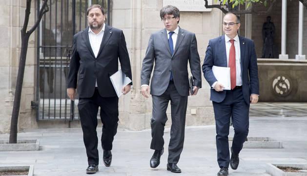 El presidente de la Generalitat, Carles Puigdemont, junto al vicepresidente, Oriol Junqueras, y el conseller de Presidencia, Jordi Turrull, este martes a su llegada a la reunión semanal del Govern, el mismo día en que expira el plazo dado por el Gobierno a la Generalitat para que justifique los gastos no esenciales.