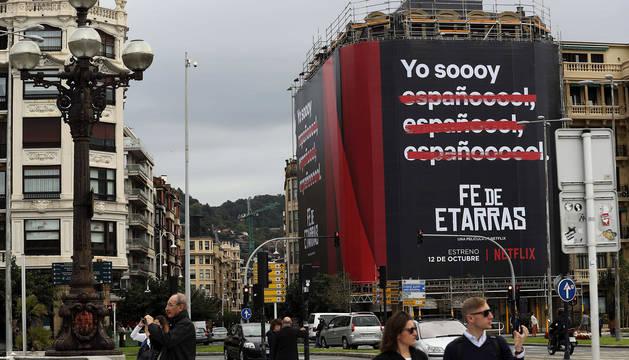Un cartel anuncia la película 'Fe de Etarras' en la fachada de un edificio del barrio de Gros de San Sebastián.