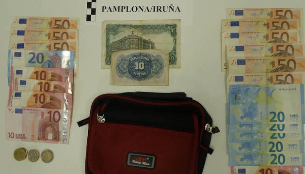 Foto de los billetes y un bolsito que portaban consigo los dos detenidos por la Policía Municipal de Pamplona tras intentar estafar a un señor de 81 con un boleto de la ONCE.