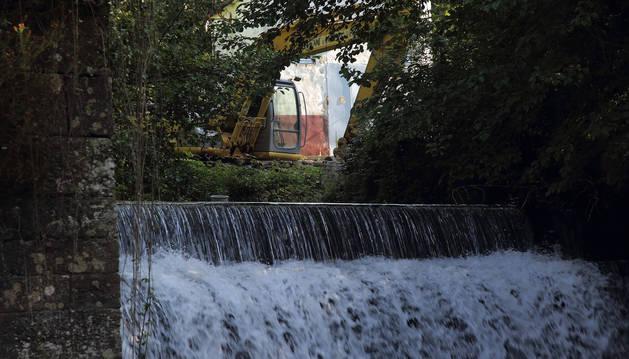 La excavadora, situada en la parte superior de la presa, en los prolegómenos de la actuación que conducirá a su desaparición.