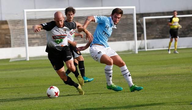 Fernando Delgado se lleva el balón ante Borja con Meseguer siguiendo la jugada desde atrás con la vista.