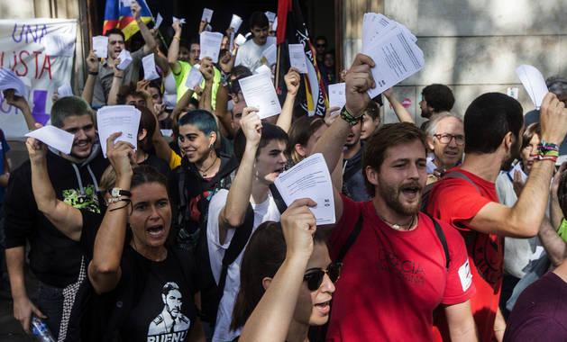 Varios estudiantes salen de la Universidad de Barcelona con papeletas del referéndum sobre la independencia de Cataluña.