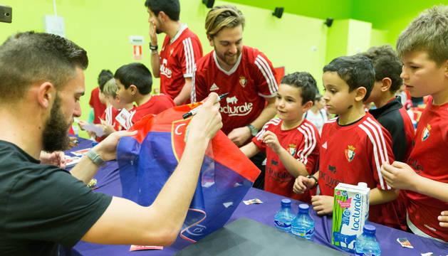 Roberto Torres firma una bandera durante uno de los múltiples actos de Fundación Osasuna.