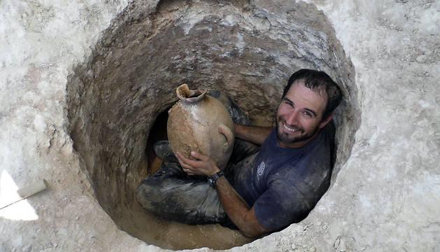 Fotografía facilitada por la Autoridad de Antigüedades de Israel, del arqueólogo David Tanami, que muestra una de las vasijas mortuarias encontradas cerca del actual Zoo Bíblico de Jerusalén.