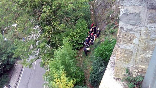 Los bomberos, durante el rescate del menor tras su caída.