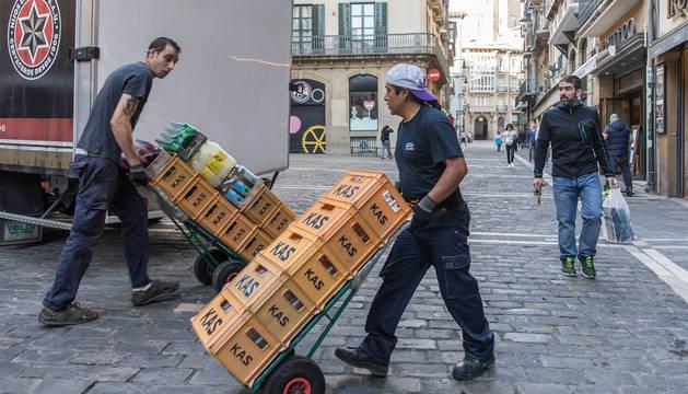 Dos repartidores con cajas de refrescos en la calle Mercaderes en una imagen tomada ayer.