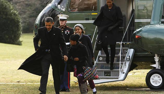 El expresidente Barack Obama y su familia bajan del helicóptero tras unas vacaciones en Hawai.