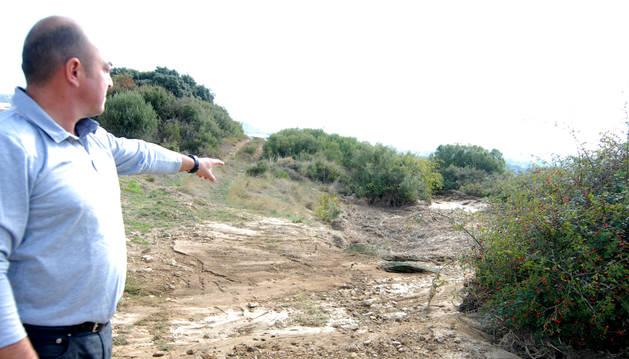 Foto del alcalde de Ujué, Rubén Sánchez, señala uno de los caminos dañados por el agua.
