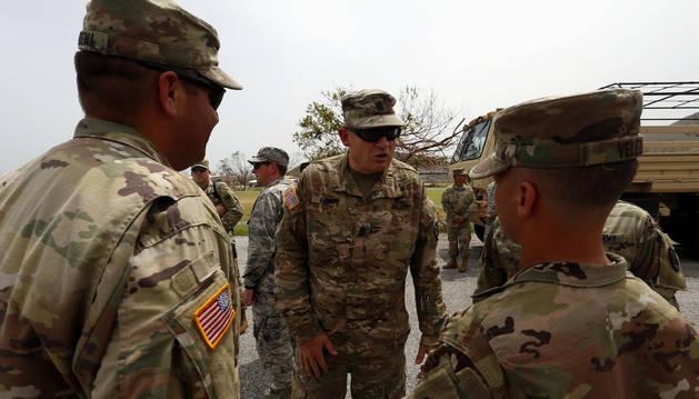 Foto de un oficial de la Guardia Nacional estadounidense habla con militares a su llegada al Campamento Santiago.