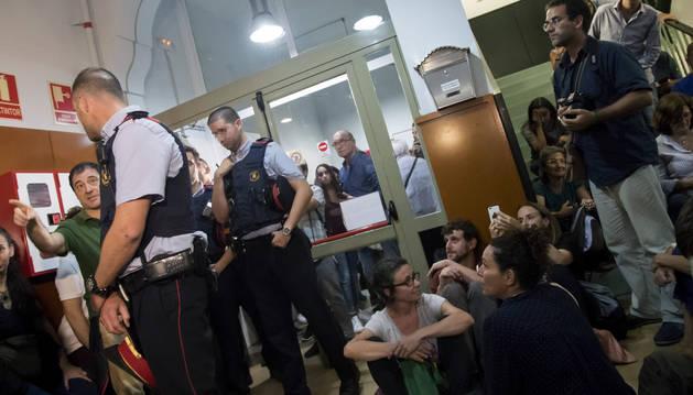 Foto de los mossos d'esquadra se presentan en el IES Tarradell, hoy en Barcelona, y le notifican al director que se debe cerrar el colegio.