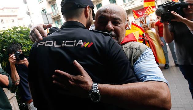 Un hombre abraza a un Policía Nacional durante la concentración en Madrid contra el referéndum en Cataluña.