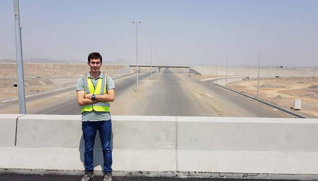 Daniel Suescun, posando en un puente desde el que se ve la traza de la autopista de ocho carriles que está construyendo la empresa Ferrovial para unir la capital omaní, Mascate, con los Emiratos Árabes Unidos.