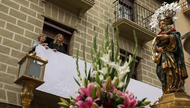 La imagen de la Virgen del Rosario, observada por dos vecinas de la localidad desde un balcón.