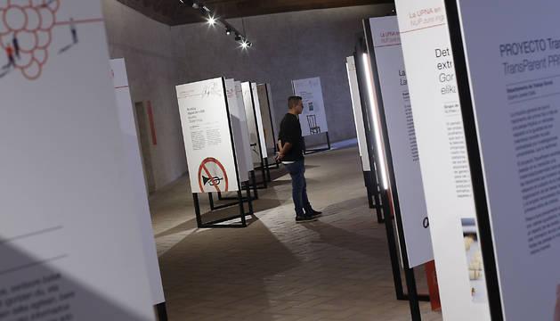 Un visitante, ante los paneles que muestran el trabajo de los departamentos de la UPNA.