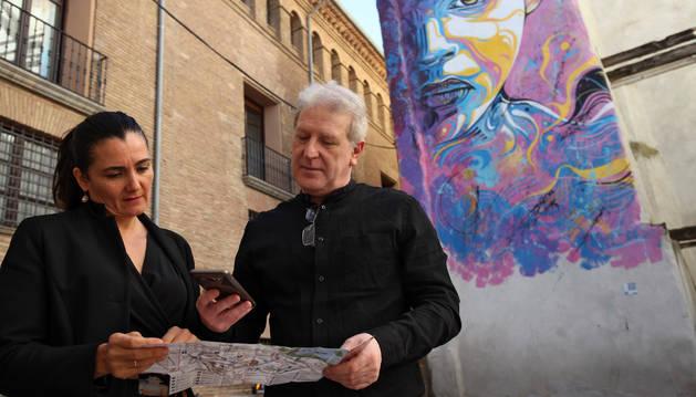 Cristina Díez y Javier Gómez, con uno de los nuevos mapas-guías y ante una obra de C215 situada en la calle Cárcel Vieja de Tudela.