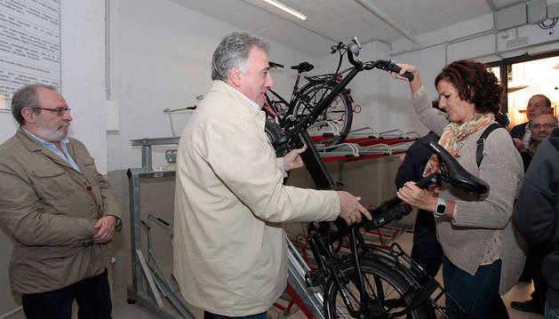 El alcalde, Joseba Asiron, descuelga una de las biciletas del aparcamiento que abrirá en octubre en Descalzos.