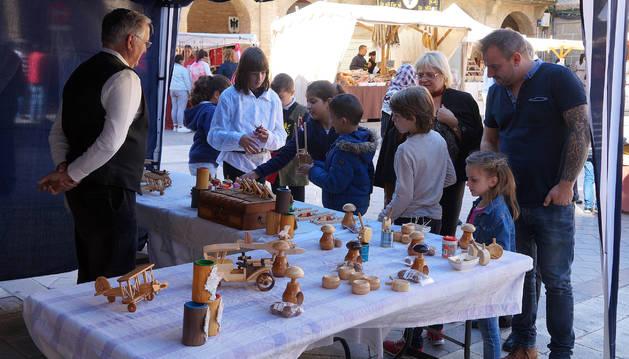 Varias personas contemplan piezas del mercado barroco.