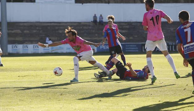 Sergio Martínez protege un balón ante la mirada de Víctor Bravo.