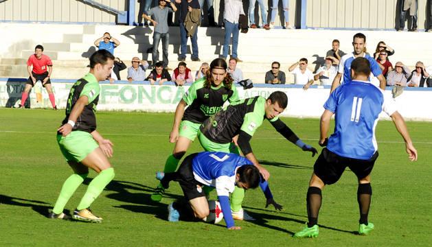 Diego Lacruz intenta, desde el suelo, llevarse un balón ante tres rivales y la atenta mirada de sus compañeros Fermín Uriz (de espaldas) y Maeztu.