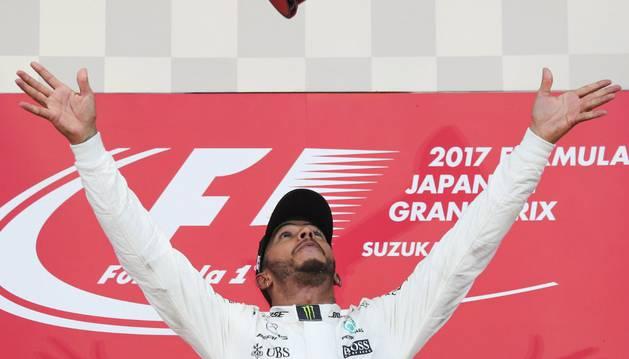 Lewis Hamilton juega con el trofeo de GP de Japón tras proclamarse campeón