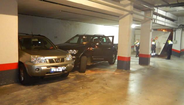Al fondo, la puerta del garaje rota y, en primer plano, el coche accidentado.