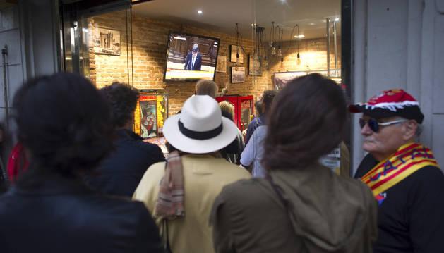 Foto de Ciudadanos escuchando el discurso del presidente de la Generalitat Carles Puigdemont en un bar cerca del Parlamento de Catalunya.