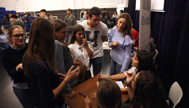 Varios alumnos piden información a representantes de una de las asociaciones participantes en la feria.