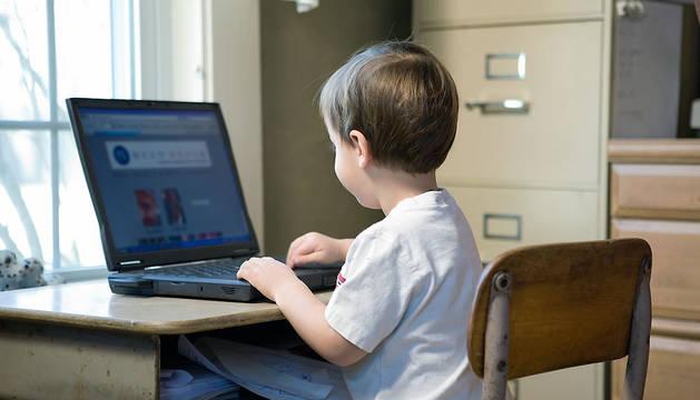 Un niño, con un ordenador portátil.