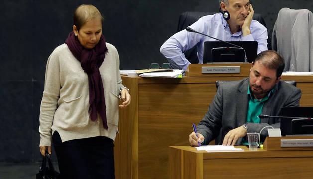 La presidenta Uxue Barkos se dirige a su escaño. Sentados, Adolfo Araiz (EH Bildu) y, tomando notas, Unai Hualde (Geroa Bai).