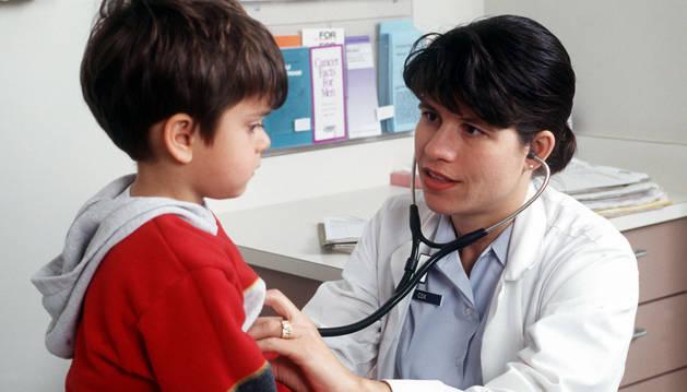 Imagen de una pediatra auscultando a un niño.