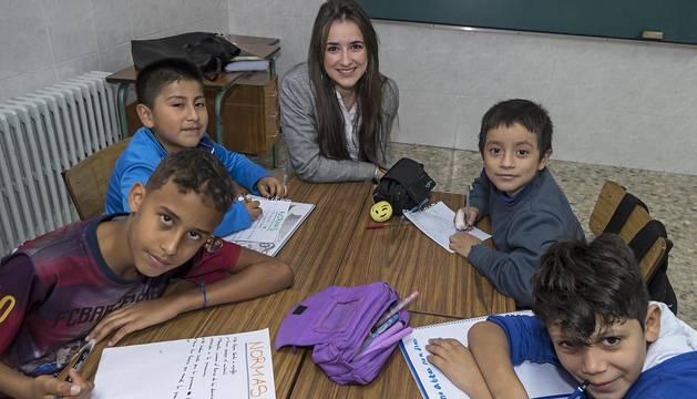 La profesora María Belarra Gorgojo con cuatro de los niños que reciben apoyo en Santa Ana (Estella).