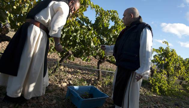 El hermano Manuel -izda.- y el hermano Daniel vendimian a mano las vides del monasterio.