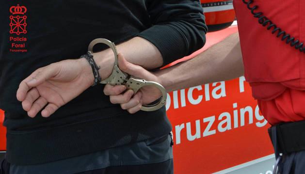 Un agente de la Policía Foral detiene a una persona.