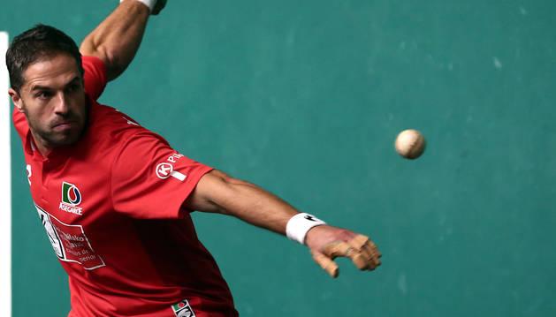 Aimar Olaizola observa la trayectoria de la pelota mientras prepara el brazo derecho para golpear la pelota.